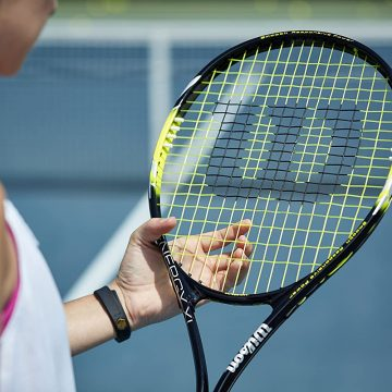 A person holding a racket on a court