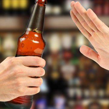 A close up of a hand holding a bottle
