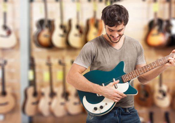 A Man testing a guitar in a store