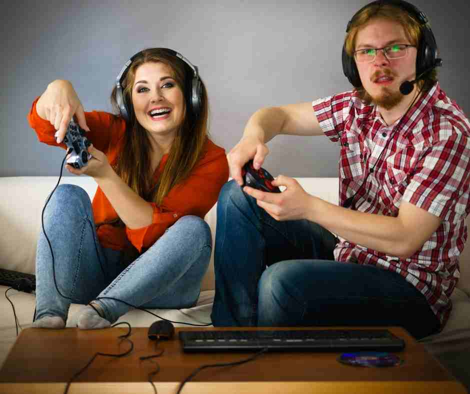 A two peoples sitting on sofa and playing video games
