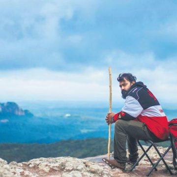 A man sitting on the mountain with bag