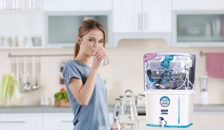 A women drinking water in front of water purifier
